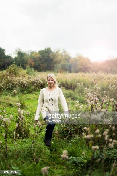 Smiling blond woman walking in the nature