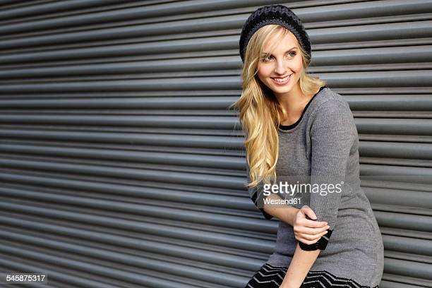 Smiling blond woman wearing knit dress and comforter standing in front of roller shutter