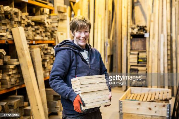 Smiling blond woman wearing work gloves standing in a workshop, holding stack of wood, looking at camera.