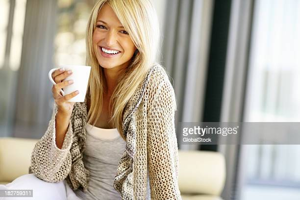 Smiling blond woman with a cup of coffee