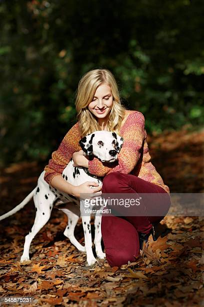 Smiling blond woman with Dalmatian in autumnal forest