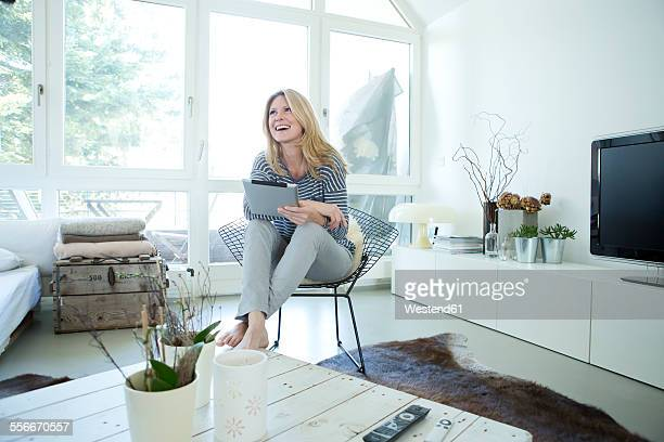 Smiling blond woman with digital tablet at home