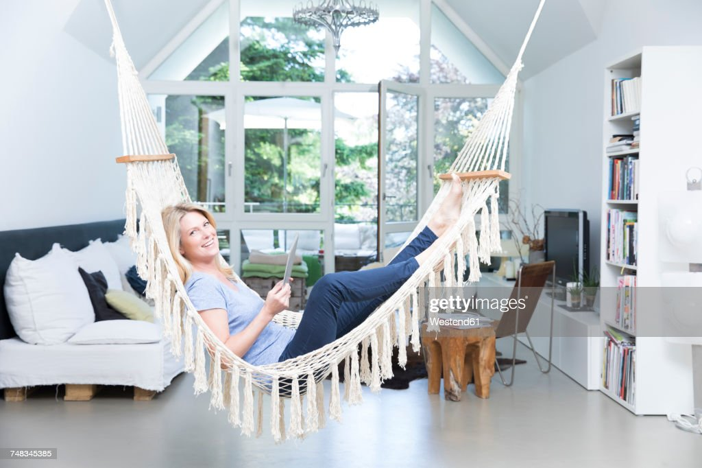 Smiling Blond Woman With Tablet Relaxing In Hammock In The Living Room