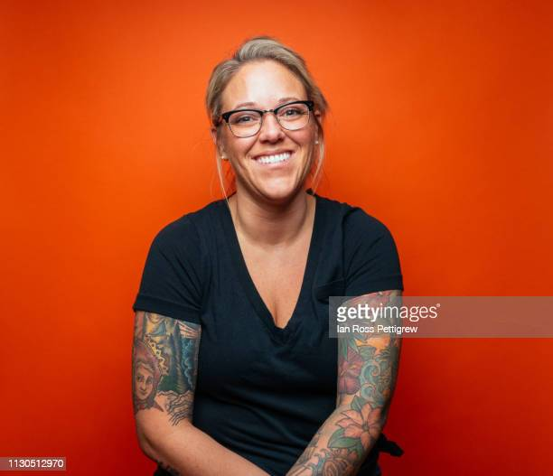 smiling blond woman with tattoos on orange background - black shirt stock pictures, royalty-free photos & images