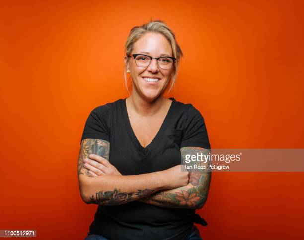smiling blond woman with tattoos on orange background - orange background stock pictures, royalty-free photos & images