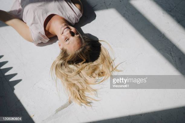 smiling blond young woman lying on the floor in sunlight - sunlight stock-fotos und bilder