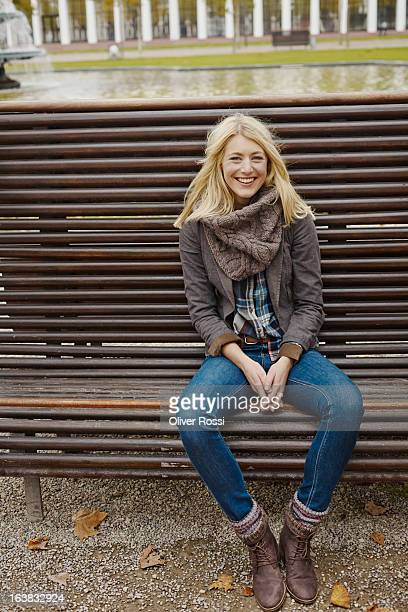 Smiling blond young woman sitting on bench
