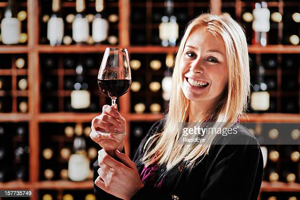 Smiling blonde beauty holds glass of red wine at winery