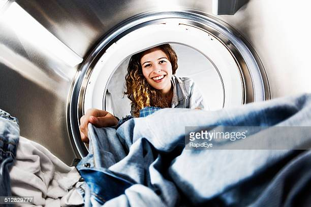 smiling blonde beauty loads her tumble dryer: seens from inside - laundry stock pictures, royalty-free photos & images