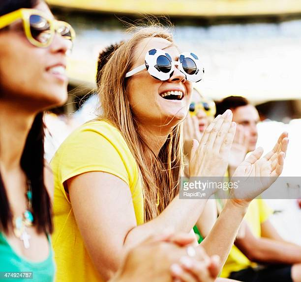 Lächelnde blonde football fan und Freunden Unterstützung für Brasilien