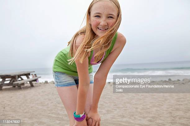 Smiling blonde teenage girl on the beach