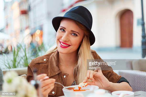 Smiling blonde woman eating soup in the outdoor restaurant