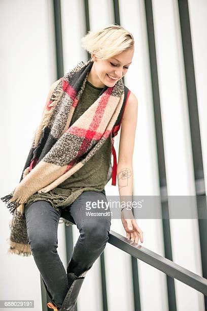 Smiling blonde woman sliding on railing