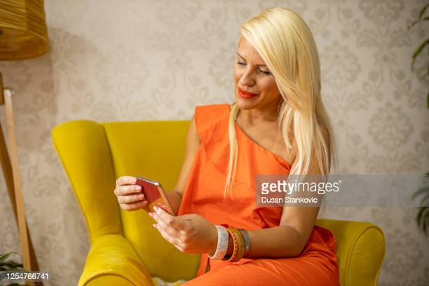 smiling blonde woman texting at home - orange dress stock pictures, royalty-free photos & images