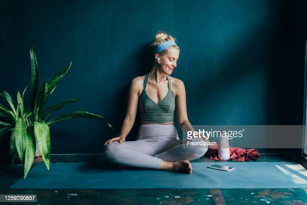 smiling blonde woman with wireless earphones using her smartphone before her home workout - active lifestyle stock pictures, royalty-free photos & images