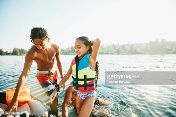 Smiling bother and sister climbing back onto boat after swimming with family in lake on summer afternoon