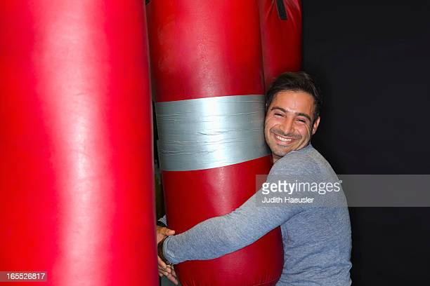 smiling boxer hugging punching bag - solo un uomo foto e immagini stock