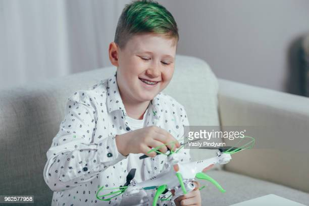 Smiling boy adjusting drone while sitting on sofa at home