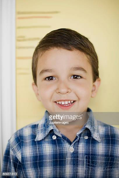 Smiling boy and measurement wall
