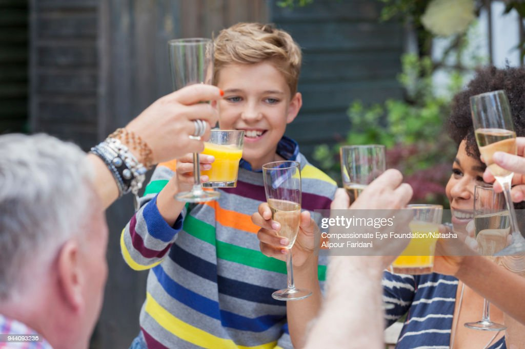 Smiling boy and multi generation family toasting champagne glasses at birthday party on patio : Stock Photo