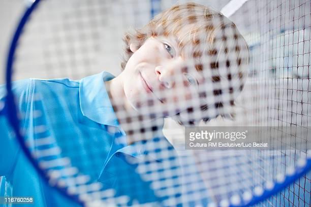 Smiling boy behind badminton racket
