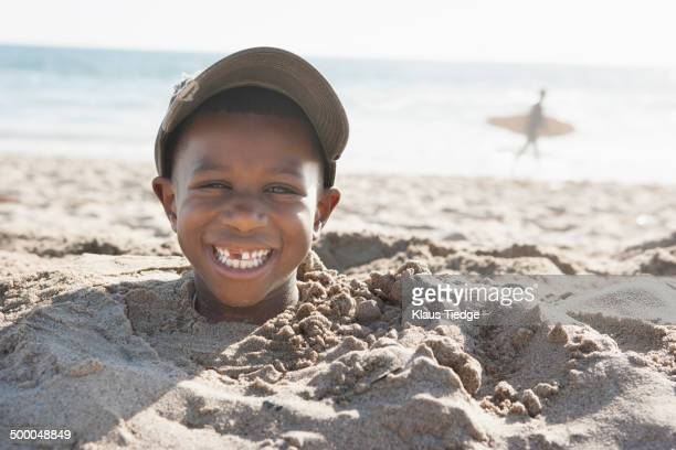 Smiling boy buried in sand on beach