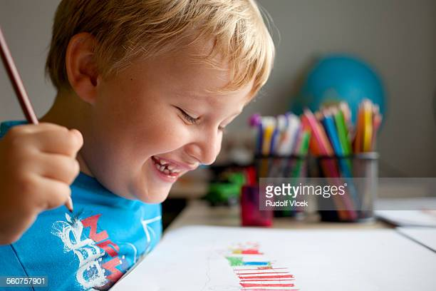 Smiling boy drawing at his desk in children's room