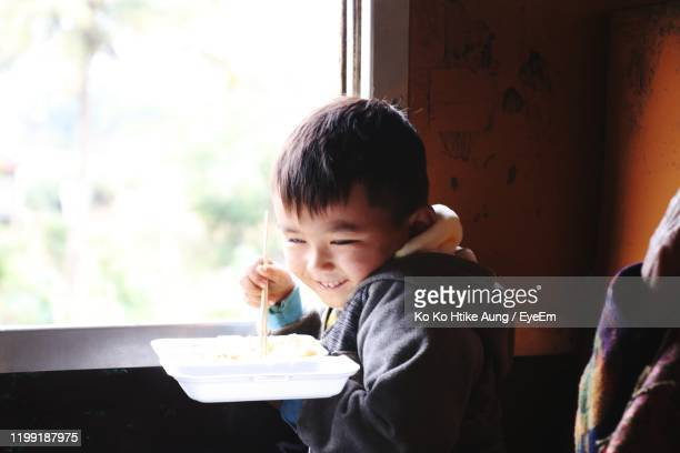 smiling boy eating food by window - ko ko htike aung stock pictures, royalty-free photos & images