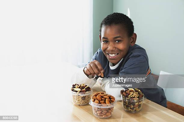 Smiling boy eating nuts