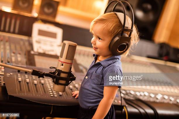 smiling boy having a radio broadcast in a station. - radio broadcasting stock pictures, royalty-free photos & images