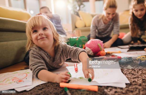 smiling boy having fun while coloring in the living room. - nanny stock photos and pictures