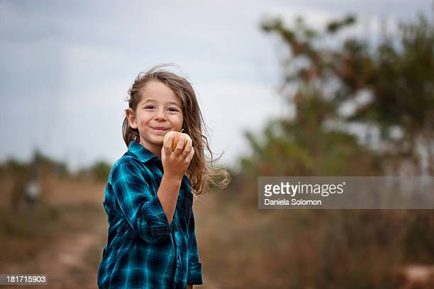 Smiling boy holding apple on country road