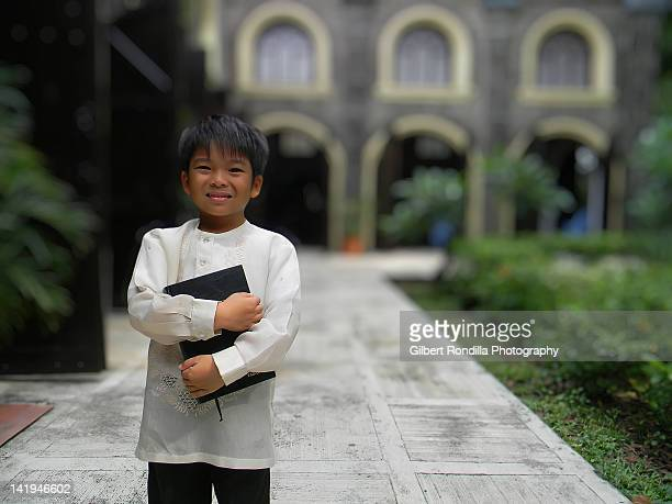 smiling boy holding bible - malabon stock pictures, royalty-free photos & images