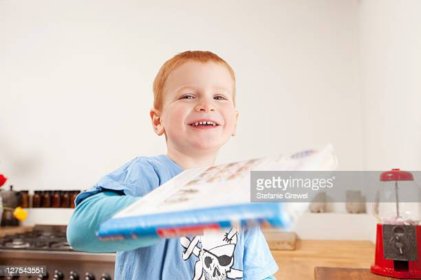 Smiling boy holding book in kitchen