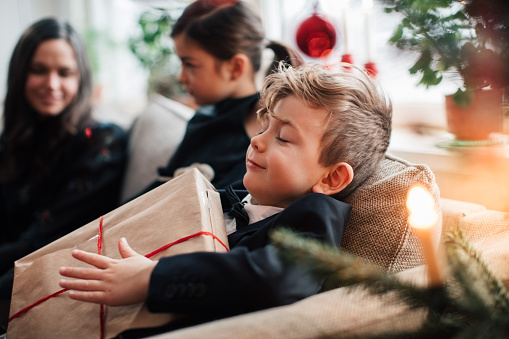 Smiling boy holding Christmas present while sitting with family in living room - gettyimageskorea
