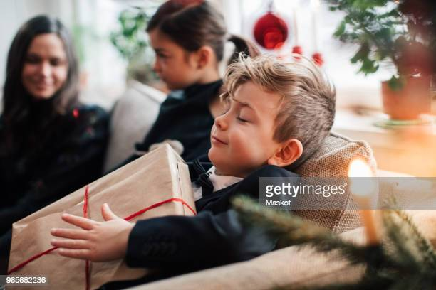 smiling boy holding christmas present while sitting with family in living room - christmas fotografías e imágenes de stock