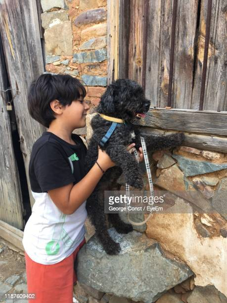 smiling boy holding dog against old abandoned house - eurasia stock pictures, royalty-free photos & images