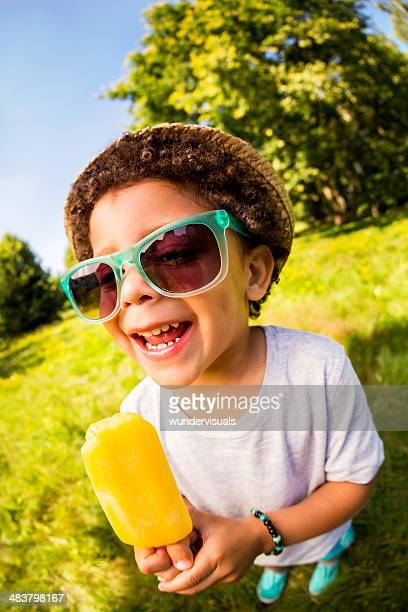 Smiling boy holding orange popsicle in park