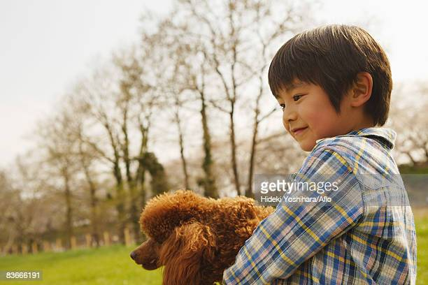 smiling boy holding pet dog - only japanese stock pictures, royalty-free photos & images