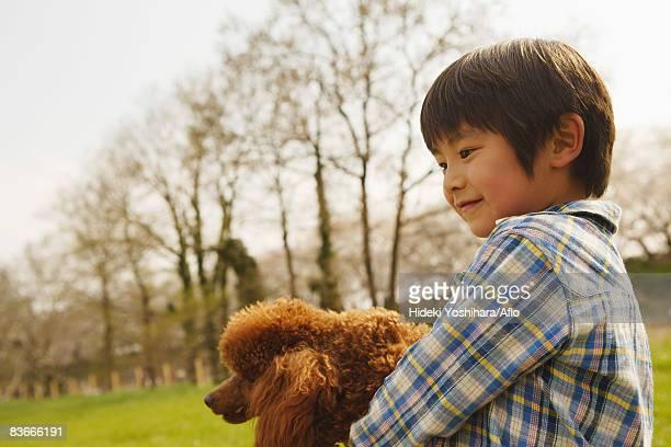 smiling boy holding pet dog - 日本人のみ ストックフォトと画像