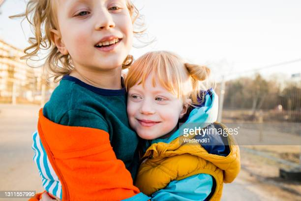 smiling boy hugging cute sister - bruder stock-fotos und bilder
