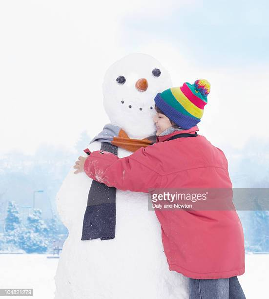 smiling boy hugging snowman - snowman stock pictures, royalty-free photos & images