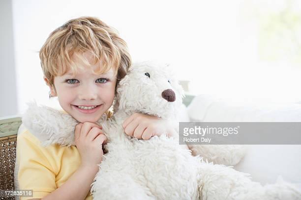 Garçon souriant embrassant ours en peluche