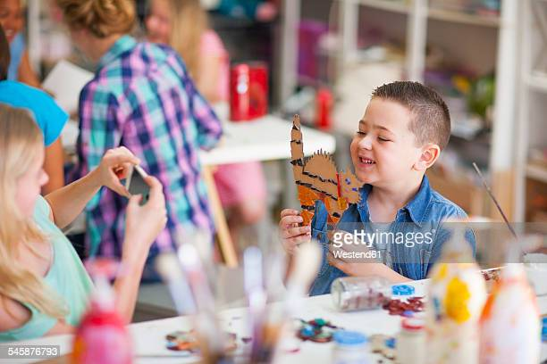 Smiling boy in arts class holding work of art