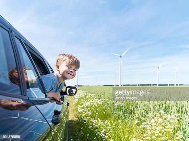 Smiling boy in car near wind turbines