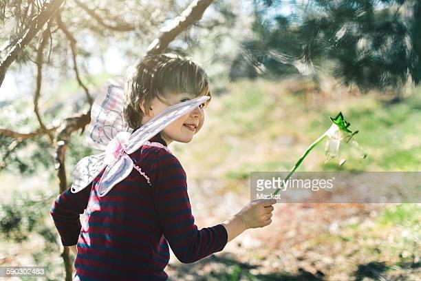 Smiling boy in fairy wings looking away at yard
