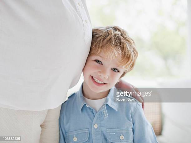Smiling boy leaning against pregnant mothers stomach