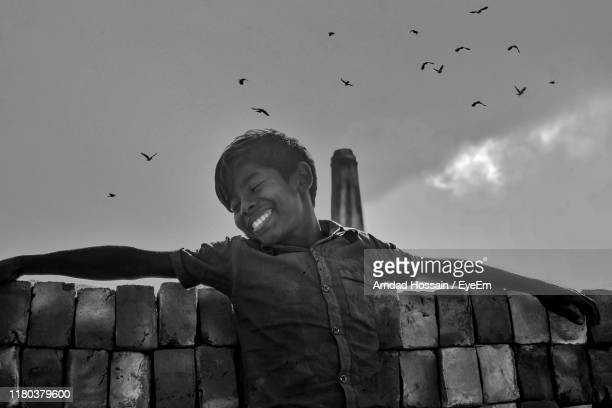 smiling boy leaning on bricks with birds flying in sky - amdad hossain stock pictures, royalty-free photos & images