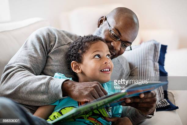 smiling boy looking at father while reading picture book at home - één ouder stockfoto's en -beelden