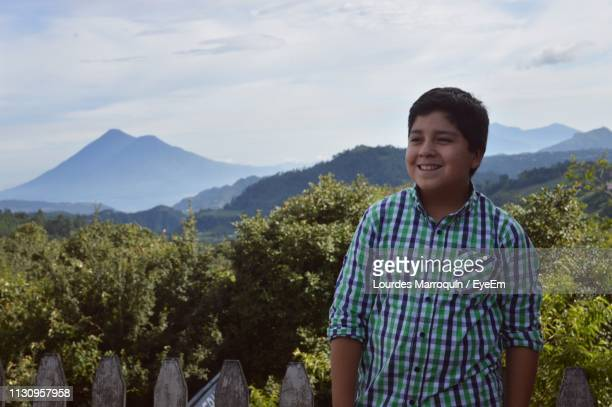 smiling boy looking away while standing against sky - quetzaltenango stock photos and pictures